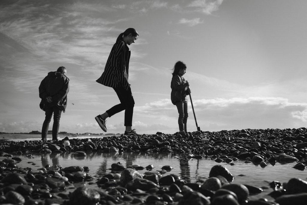 Reportage de famille à Plozevet. Photographie en noir et blanc d'un groupe de 3 personnes recherchant des coquillages sur la plage. Séance reportage de famille.