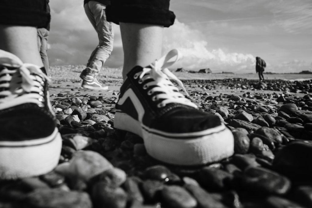 Reportage de famille à Plozevet. Photographie en noir et blanc au ras du sol, gros plan sur les pieds.