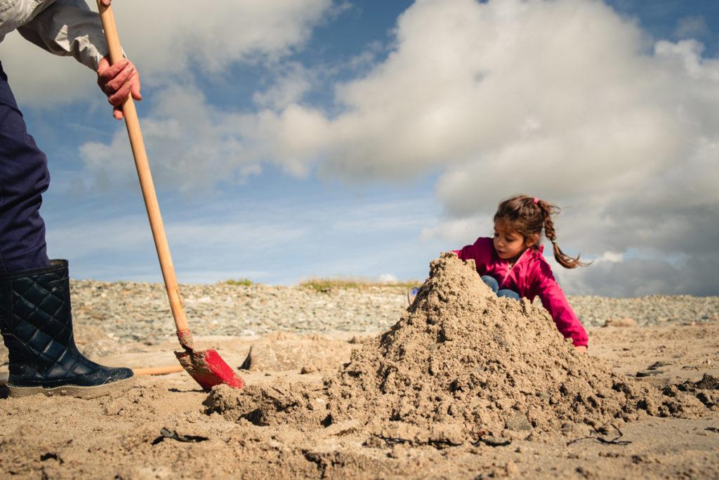 Reportage de famille à Plozevet. Une enfant et un adulte construisent un château de sable Séance reportage de famille.