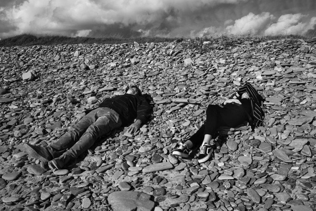Reportage de famille à Plozevet. Photographie en noir et blanc d'un père et sa fille faisant la sieste sur les galets. Séance de famille.