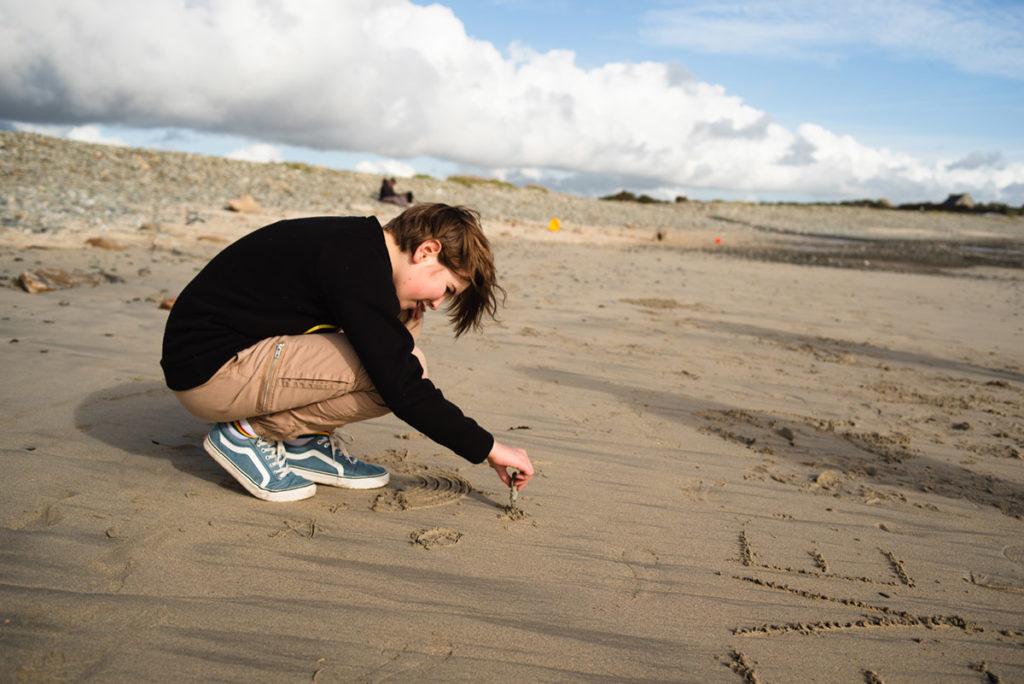 Reportage de famille à Plozevet. Jeune fille dessinant dans le sable avec un galet. Séance de famille.