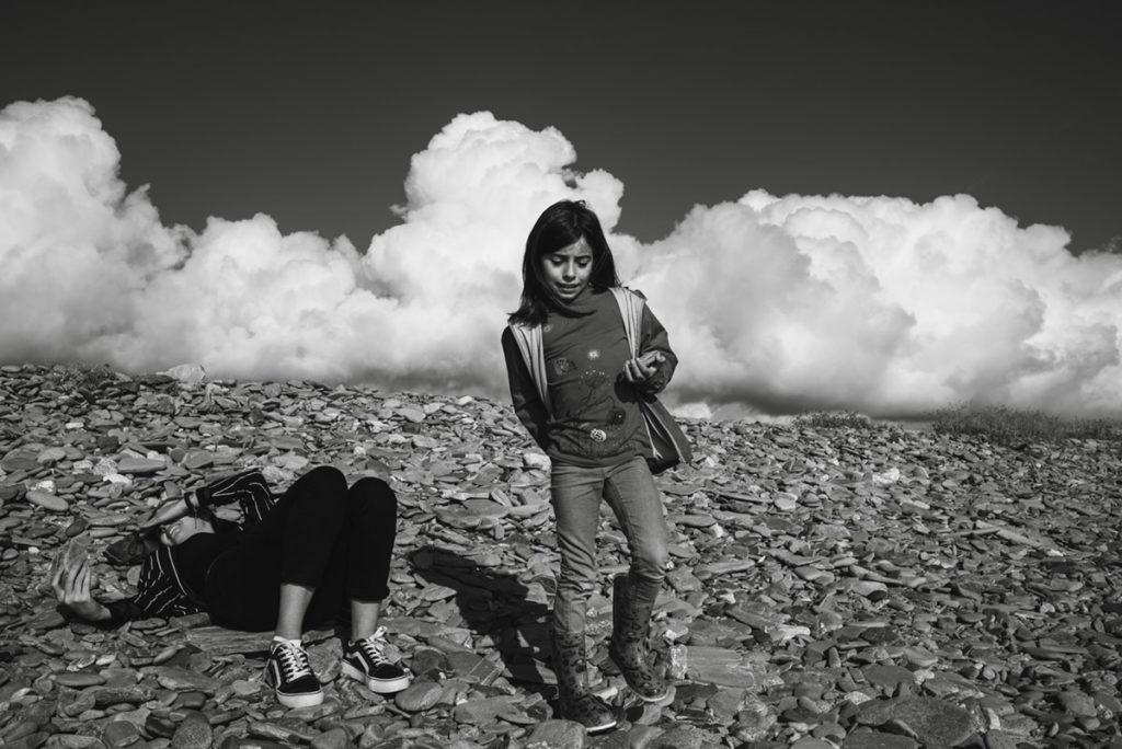 Reportage de famille à Plozevet. Photographie en noir et blanc de deux jeunes filles sur les galets, une allongée regardant son téléphone, l'autre plus jeune ramassant des galets. Séance famille.