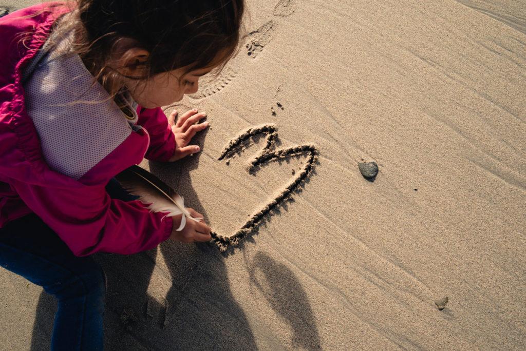 Reportage de famille à Plozevet. Jeune enfant dessinant dans le sable avec une plume. Séance famille