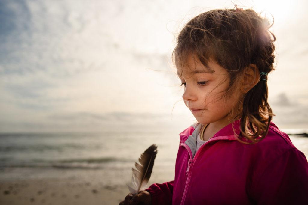 Reportage de famille à Plozevet. Portrait d'une jeune enfant  en contre-jour, soleil dans les cheveux. Séance famille.
