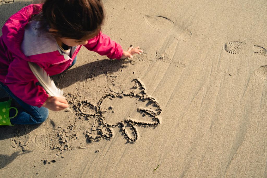 Reportage de famille à Plozevet. Jeune enfant dessinant sur le sable avec une plume. Séance de famille.