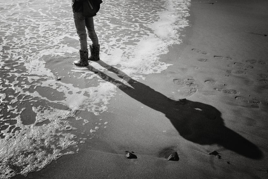 Reportage de famille à Plozevet. Photographie sur la plage lors d'un reportage de famille, ombre d'un enfant.