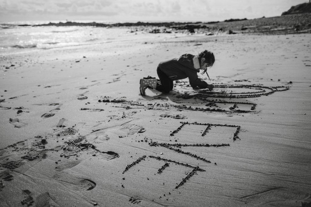 Reportage de famille à Plozevet. Photographie en noir et blanc d'une enfant écrivant son prénom sur le sable. Séance de famille.