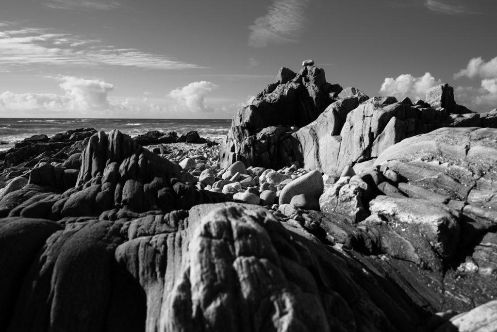 Reportage de famille à Plozevet. Vue en noir et blanc des rochers et de la mer.