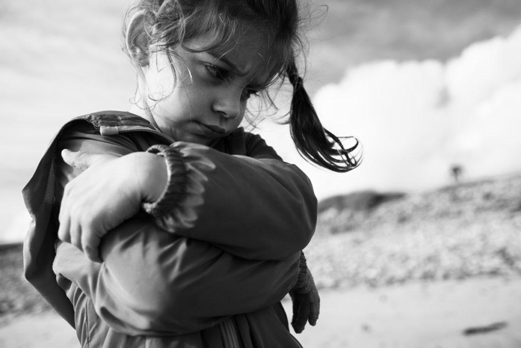 Reportage de famille à Plozevet. Photographie en noir et blanc d'une enfant qui boude. Portrait assez rapproché.