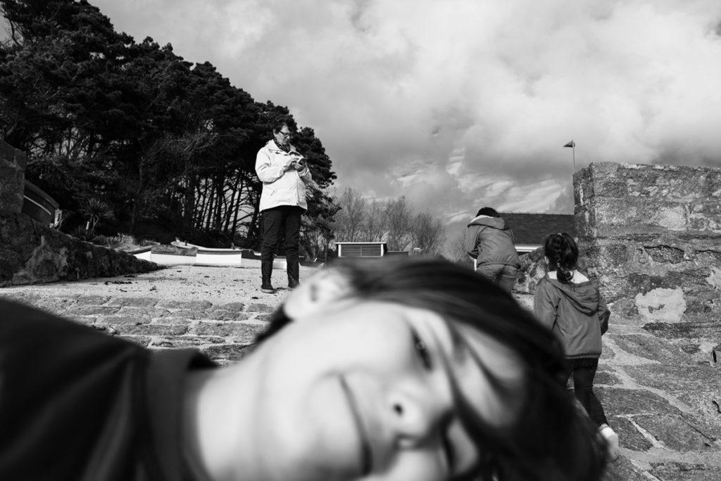 Reportage de famille à Plozevet. Photographie en noir et blanc d'une famille dont une personne passe devant l'objectif. Séance de famille.