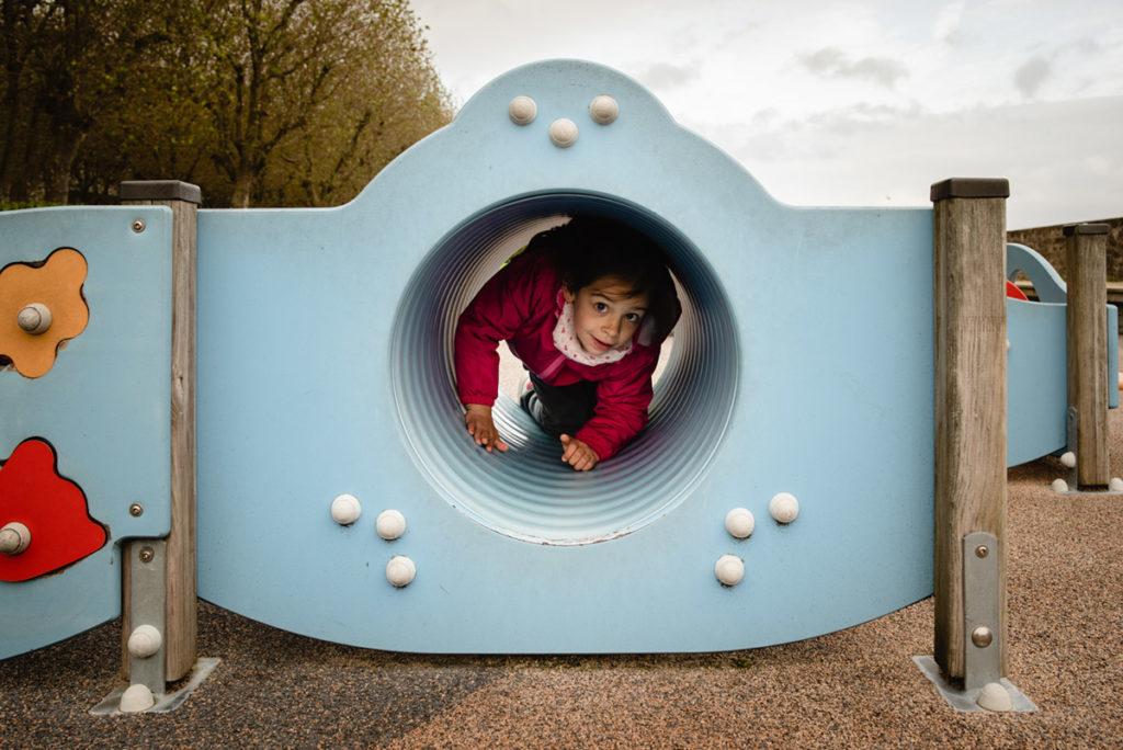 Reportage de famille à Plozevet. Photographie d'une enfant jouant dans un parc, à l'intérieur d'un tube. Séance reportage de famille.