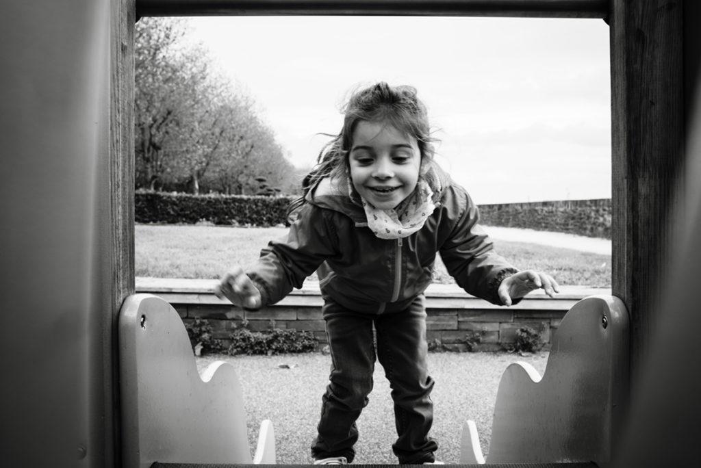 Reportage de famille à Plozevet. Photographie en noir et blanc d'une enfant jouant sur un tobbogan. Séance reportage de famille.