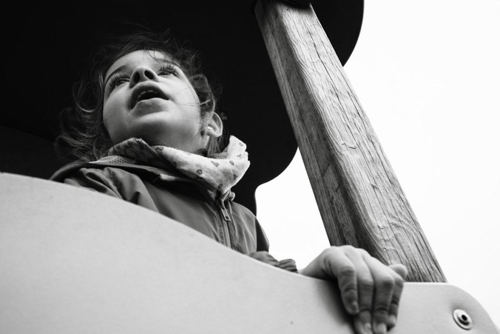 Reportage de famille à Plozevet. Photographie en noir et blanc d'une enfant dans un tobbogan. Séance reportage de famille.