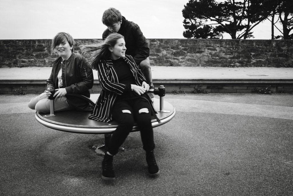 Reportage de famille à Plozevet. Photographie en noir et blanc d'ados sur un tourniquet. Séance reportage de famille.
