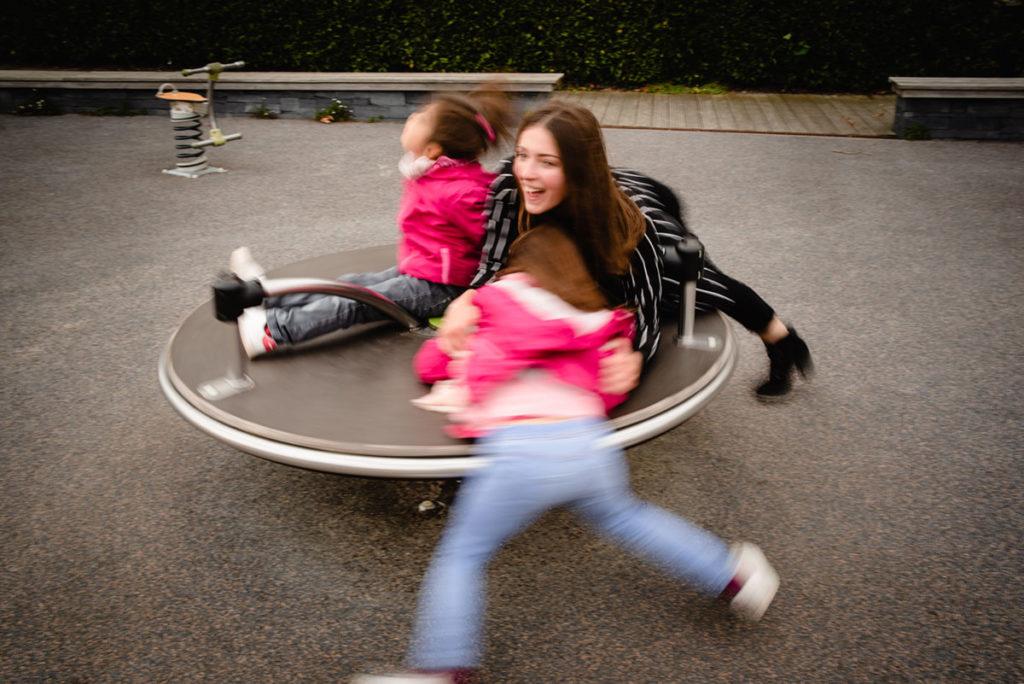 Reportage de famille à Plozevet. Photographie en pose lente d'enfants sur un tourniquet. Séance reportage de famille.