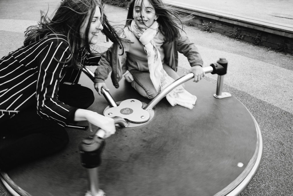 Reportage de famille à Plozevet. Photographie en noir et blanc d'une enfant et d'une jeune fille sur un tourniquet. Les cheveux sont soulevés par le vent. Séance reportage de famille.