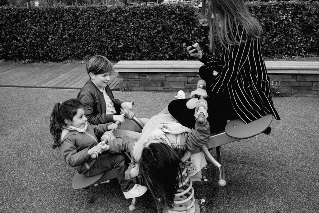 Reportage de famille à Plozevet. Photographie en noir et blanc d'un groupe d'enfants jouant sur un jeu à bascule dans un parc. Séance reportage de famille.
