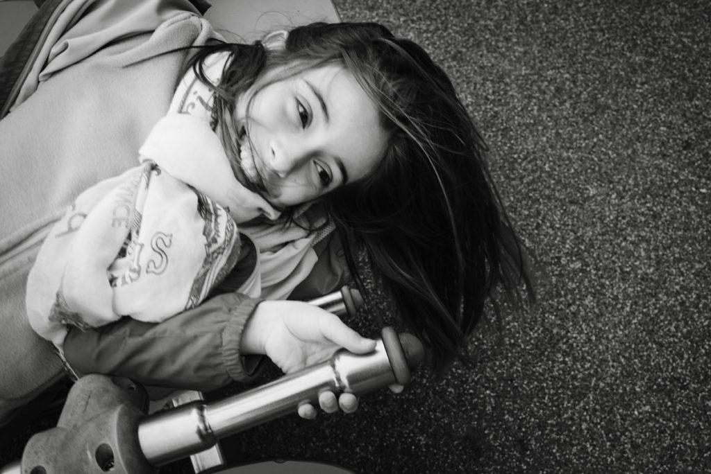 Reportage de famille à Plozevet. Portrait en noir et blanc d'une enfant jouant dans un parc. Séance reportage de famille.