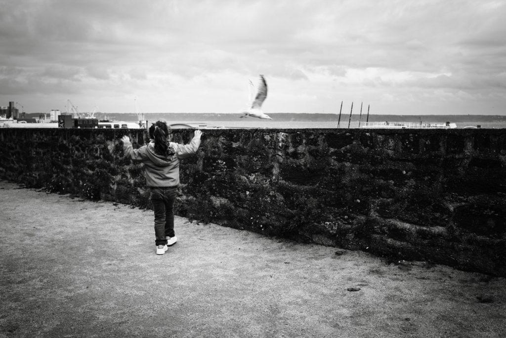 Reportage de famille à Plozevet. Photographie en noir et blanc d'une enfant essayant d'attraper une mouette . Séance reportage de famille.