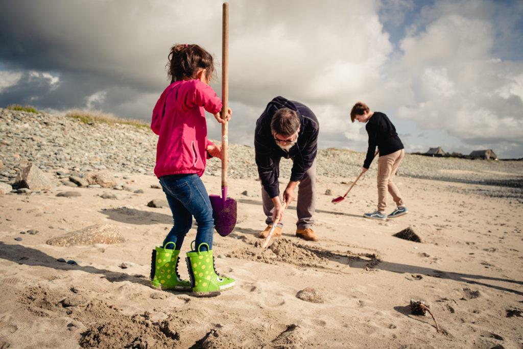 Reportage de famille à Plozevet. Enfants et adulte construisant ensemble un château de sable sur la plage.