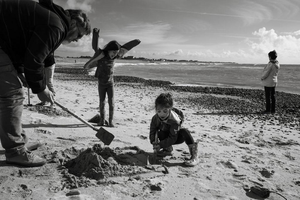 Reportage de famille à Plozevet. Joie de l'enfance lors de la construction d'un château sur la plage.