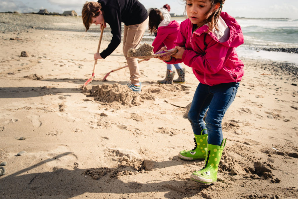 Reportage de famille à Plozevet. Portrait d'une enfant creusant le sable avec sa pelle sur la place lors de séance de photo en famille.