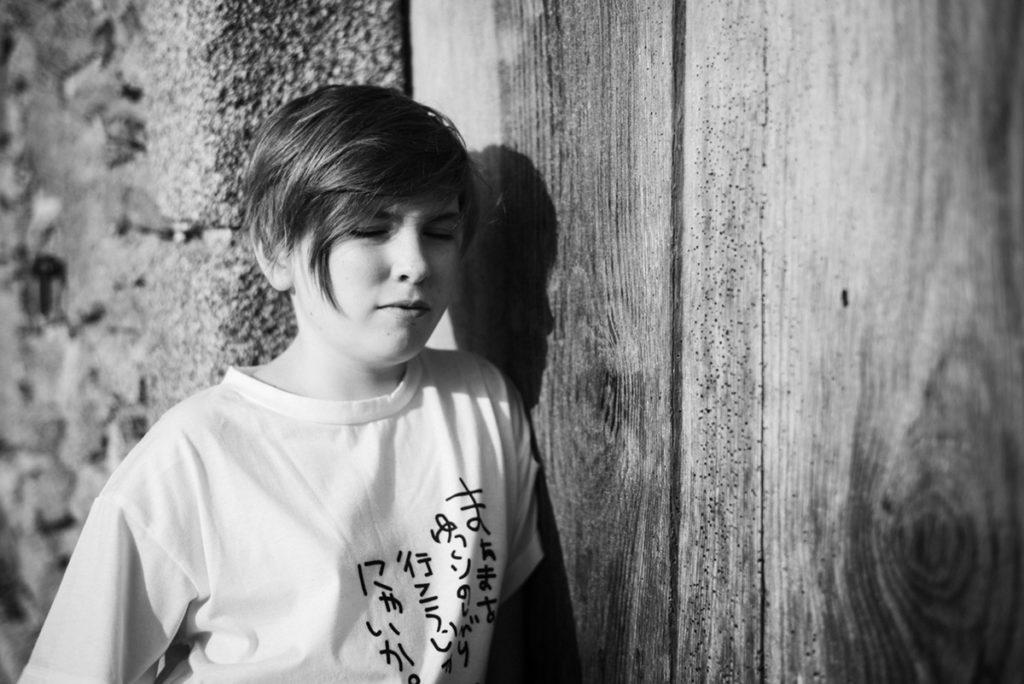 Rétrospective 2019, mes photos préférés ! Portrait en noir et blanc d'une jeune fille près d'une vieille porte en bois Photographe Pascaline Michon.