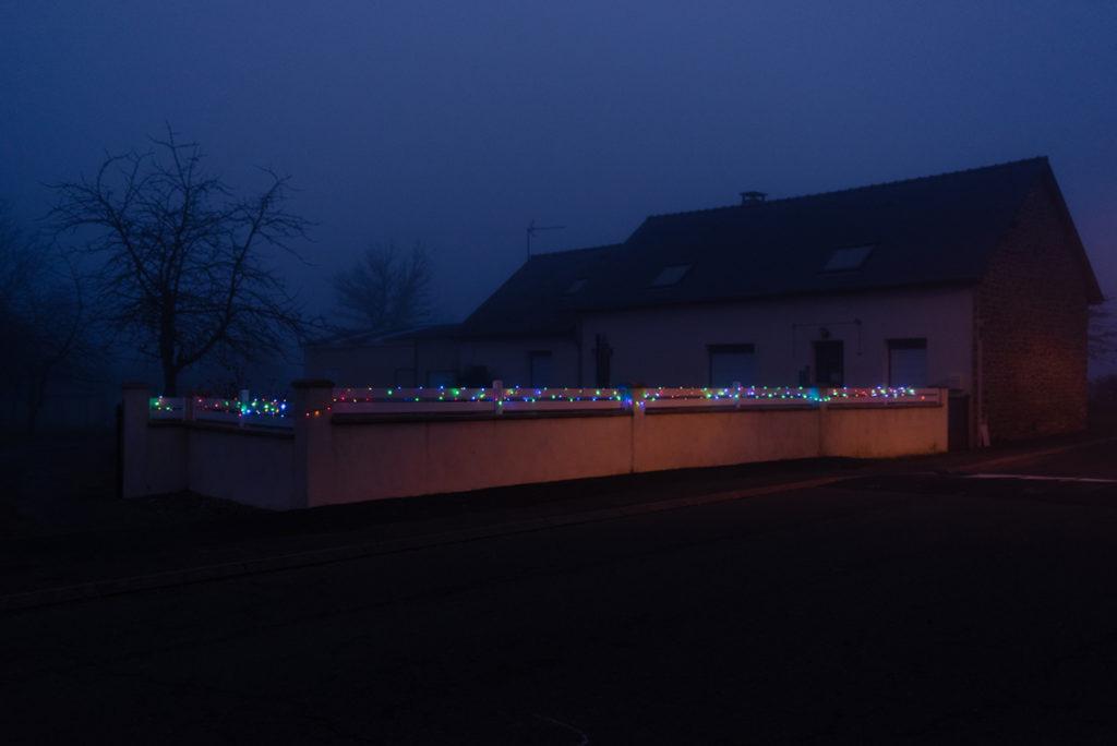 Photographier de nuit dans le brouillard. Photographie de nuit dans un village éclairé en Mayenne. On voit une guirlande lumineuse sur le mur d'une maison.