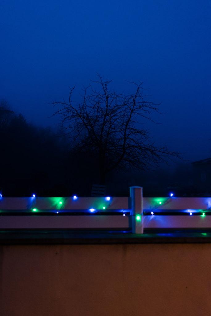 Photographier de nuit dans le brouillard. Photographie de nuit dans un village éclairé en Mayenne. Photographie d'un arbre qui se détache sur le bleu nuit du ciel. Le mur au premier plan est décorée d'une guirlande lumineuse.