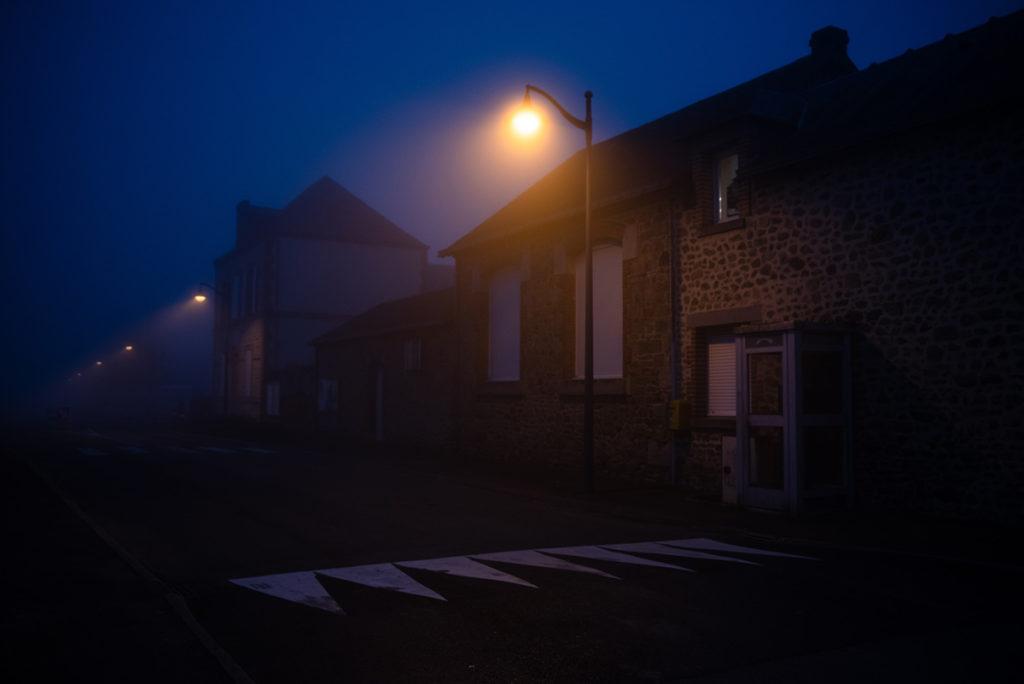 Photographier de nuit dans le brouillard. Photographie de nuit dans un village éclairé en Mayenne.