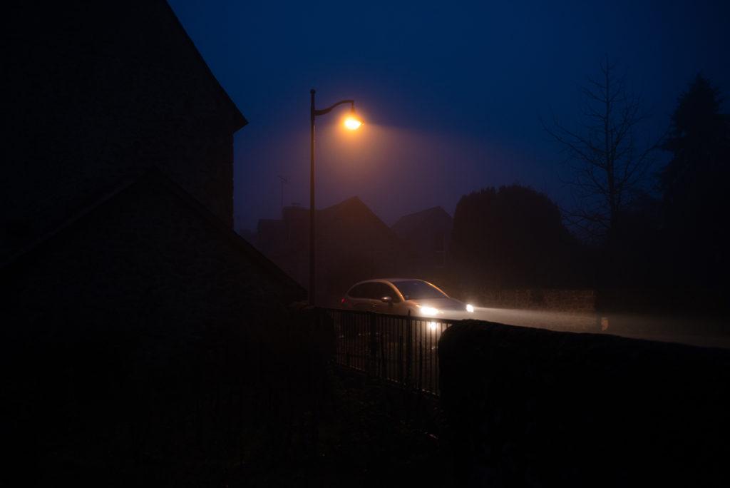 Photographier de nuit dans le brouillard. Photographie de nuit dans un village éclairé en Mayenne. Une voiture passe, on distingue la trainée des phares.