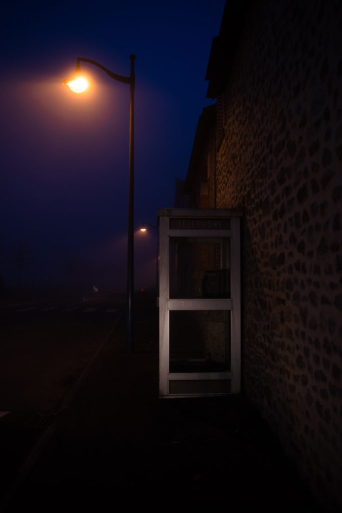 Photographier de nuit dans le brouillard. Photographie de nuit dans un village éclairé en Mayenne. La cabine téléphonique est éclairée par des phares de voiture.