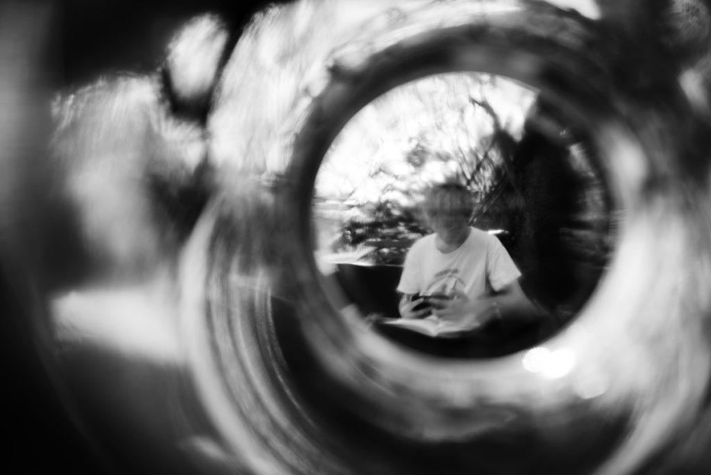 Rétrospective 2019, mes photos préférés ! Reportage de famille en Mayenne. Portrait créatif en noir et blanc d'un ado révisant dans son jardin. Photographe Pascaline Michon.