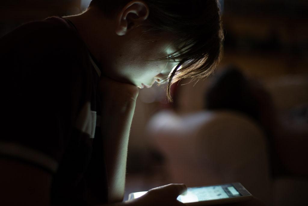 Rétrospective 2019, mes photos préférés ! Reportage de famille en Mayenne. Portrait en contre-jour d'une jeune fille qui regarde sa tablette. Photographe Pascaline Michon.