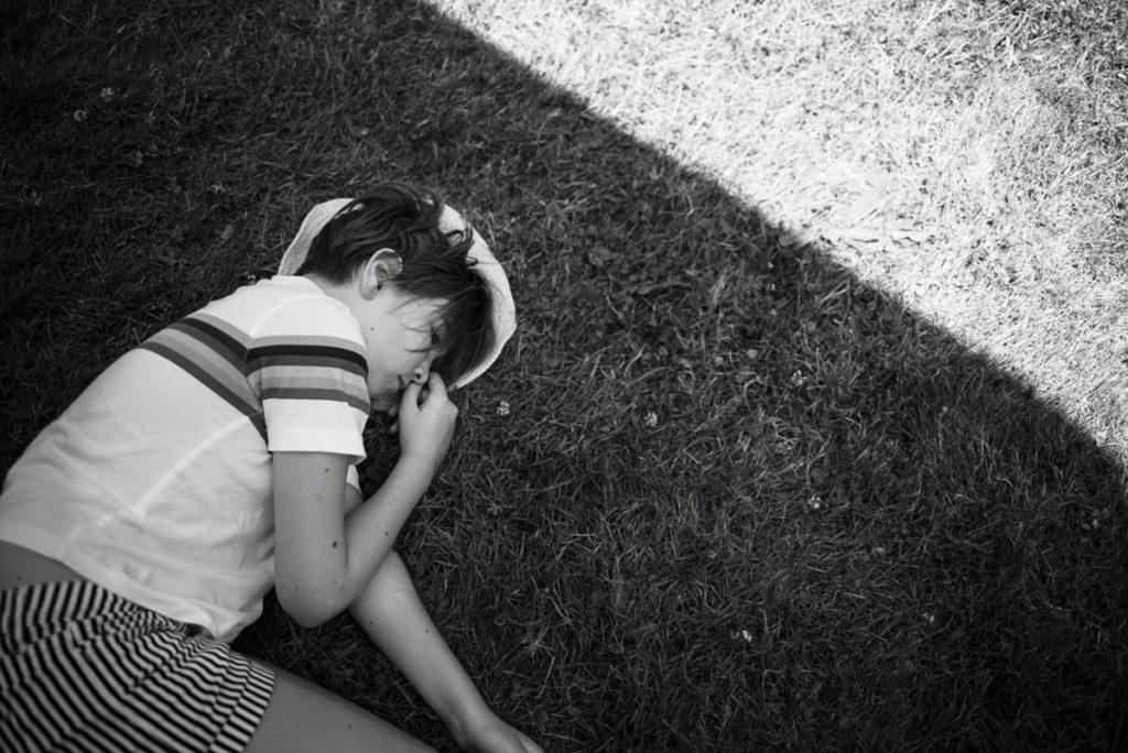 Rétrospective 2019, mes photos préférés ! Reportage de famille en Mayenne. Portrait en noir et blanc d'une jeune fille allongée dans l'herbe, en été dans son jardin. Photographe Pascaline Michon.