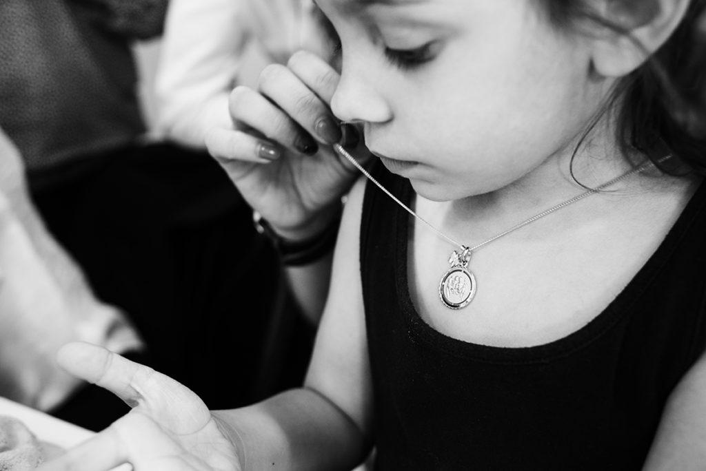 Rétrospective 2019, mes photos préférés ! Reportage de famille dans la Sarthe. Portrait en noir et blanc d'une enfant à qui on accroche sa médaille de baptême. Photographe Pascaline Michon.