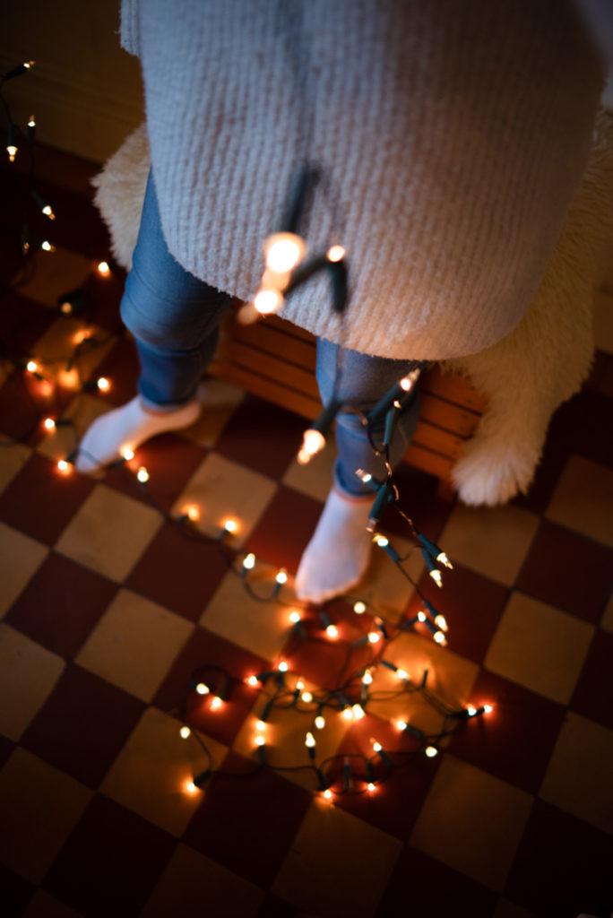 Rétrospective 2019, mes photos préférés ! Reportage de famille en Mayenne. Portrait d'une jeune fille démêlant une guirlande électrique pour décorer le sapin de Noël. Photographe Pascaline Michon.