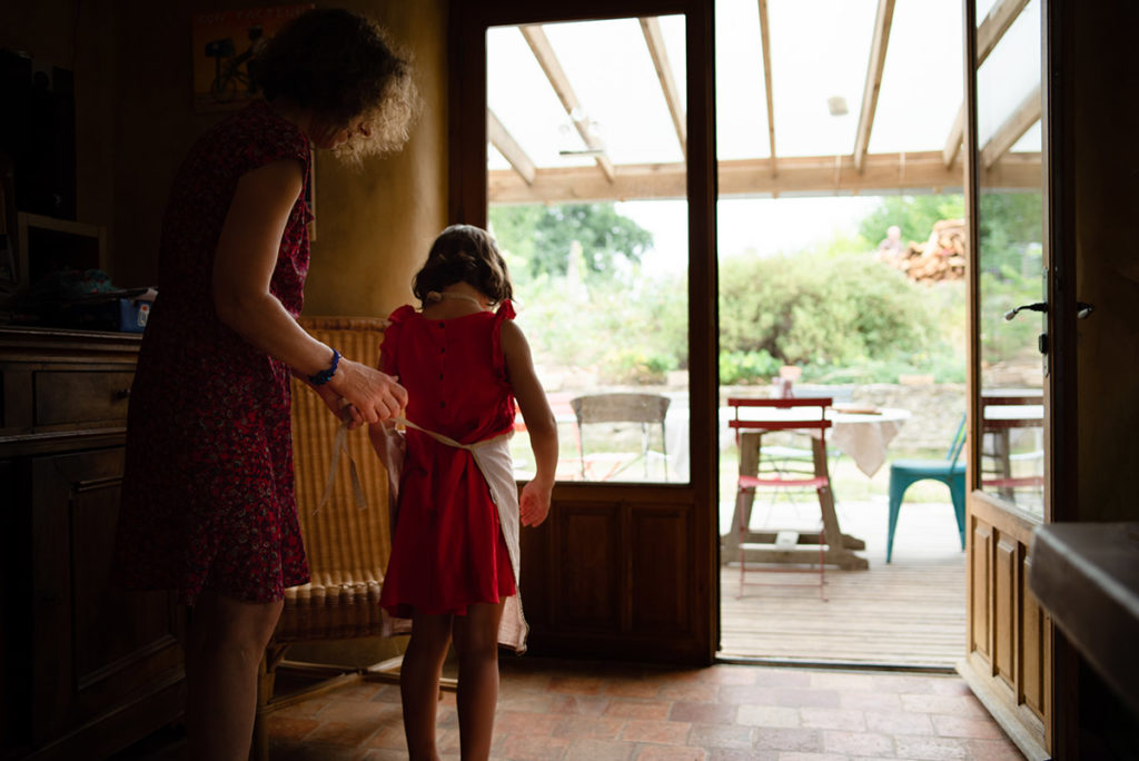 Rétrospective 2019, mes photos préférés ! Reportage de famille en Mayenne. Scène de vie du quotidien, une maman attache un tablier à sa fille qui s'apprête à faire un gateau. Photographe Pascaline Michon.