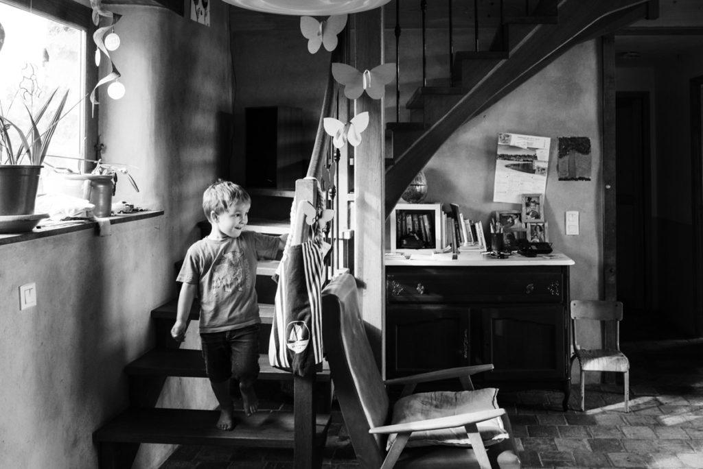 Pourquoi je fais le choix de la photographie en noir et blanc ? Photographie en noir et blanc, reportage de famille. Un jeune enfant descend les escaliers, on devine sa joie.