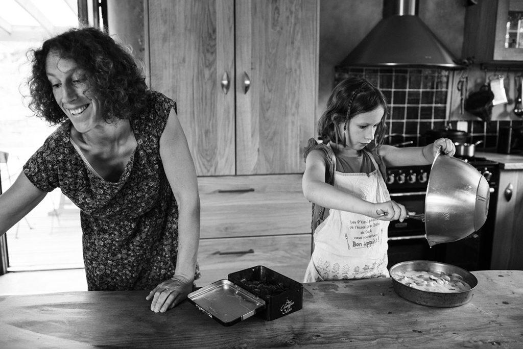 Pourquoi je fais le choix de la photographie en noir et blanc ? Photographie en noir et blanc d'une scène de vie de famille. Reportage du quotidien, une maman prépare un gâteau avec sa fille.