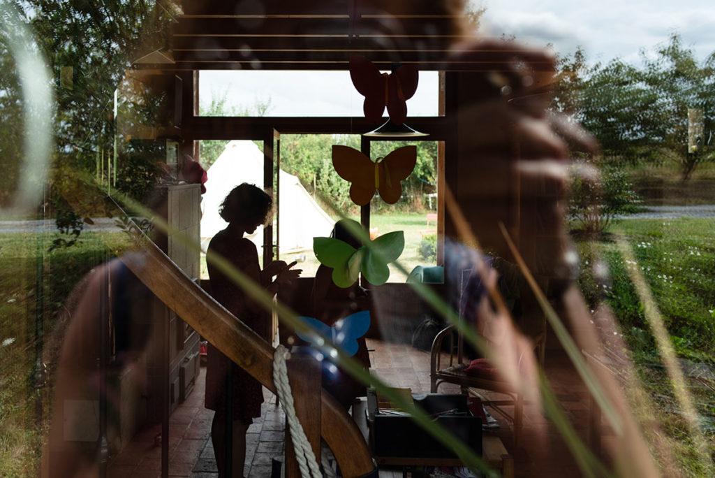 Rétrospective 2019, mes photos préférés ! Reportage de famille en Mayenne. Photographie prise à travers une fenêtre d'une scène de vie du quotidien. La photo mêle intérieur et extérieur par le jeu des reflets. Photographe Pascaline Michon.