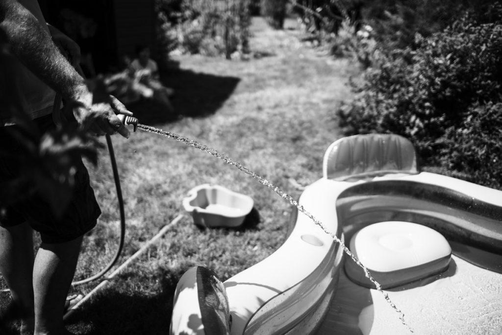 Pourquoi je fais le choix de la photographie en noir et blanc ? Reportage de famille en été. Photographie en noir et blanc du remplissage d'une petite piscine.
