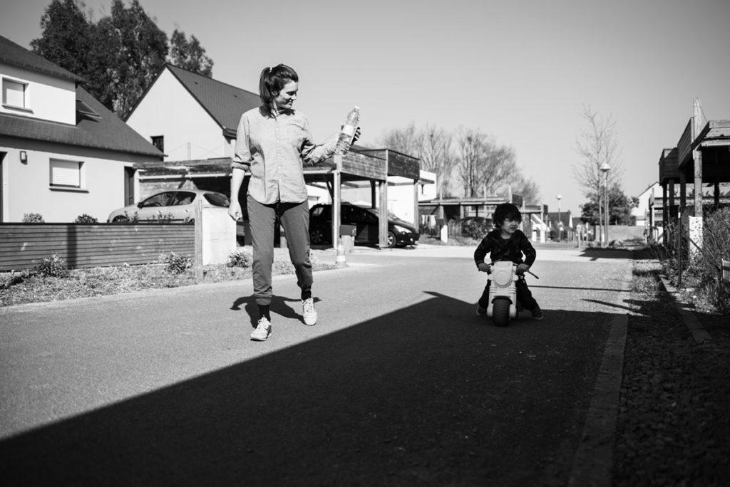 Pourquoi je fais le choix de la photographie en noir et blanc ? Une maman accompagne  son fils sur sa petite moto. Reportage de famille.