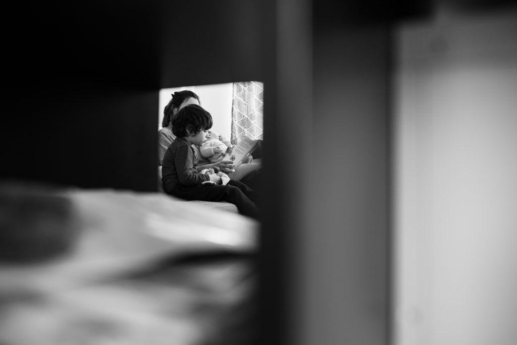 Pourquoi je fais le choix de la photographie en noir et blanc ? Photographie en noir et blanc d'un moment de lecture entre une mère et son fils. Reportage de famille.