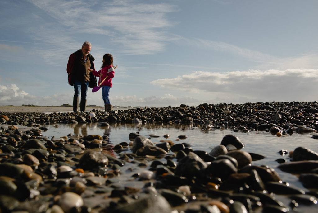 Rétrospective 2019, mes photos préférés ! Reportage de famille dans le Finistère. Scène de vie en bord de mer : une jeune fille montre le coquillage qu'elle vient de ramasser à son grand-père. Photographe Pascaline Michon.