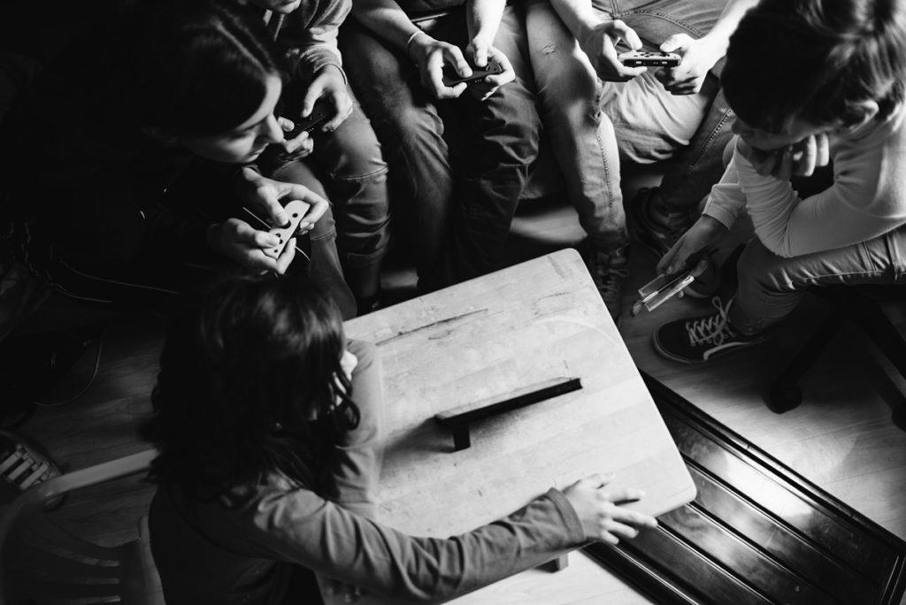 Rétrospective 2019, mes photos préférés ! Reportage de famille en Sarthe. Portrait en noir et blanc : des enfants et ados sont rassemblés autour d'un jeu vidéo. Photographe Pascaline Michon.