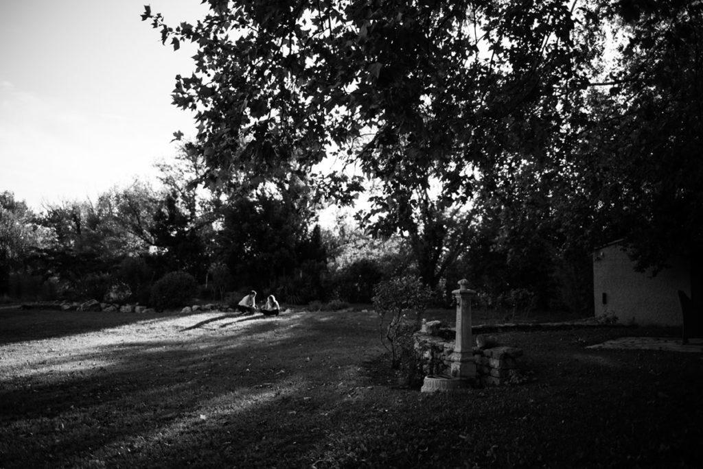 Pourquoi je fais le choix de la photographie en noir et blanc ? Photographie en noir et blanc d'une scène de vie dans un jardin en été au soleil couchant.
