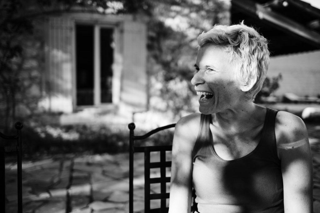 Pourquoi je fais le choix de la photographie en noir et blanc ? Portrait en noir et blanc d'une jeune femme souriante, entre ombre et lumière. Reportage de famille.