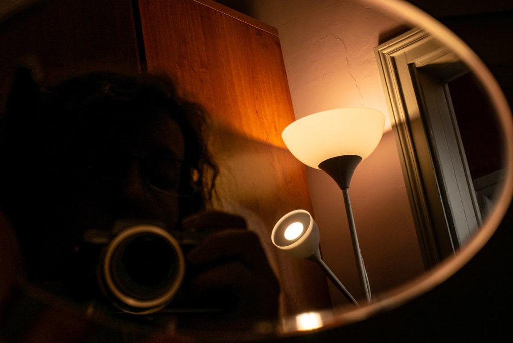 Mes autoportraits en 2019. Autoportrait dans un miroir en clair-obscur. On devine juste mes cheveux et mon appareil photo. Photographe Pascaline Michon.