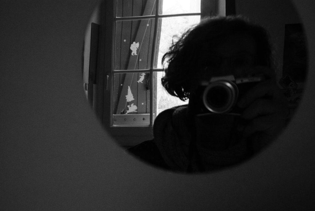 Mes autoportraits en 2019. Autoportrait dans un miroir rond, en noir et blanc. On devine les décorations de Noël sur la fenêtre qui se reflète. Photographe Pascaline Michon.